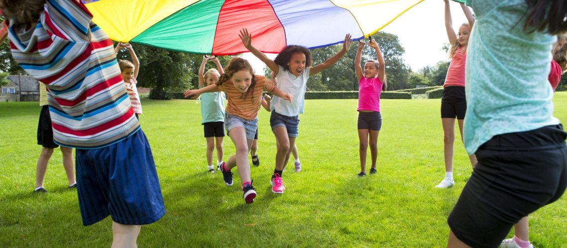 Children playing a game with a colourful Parachute