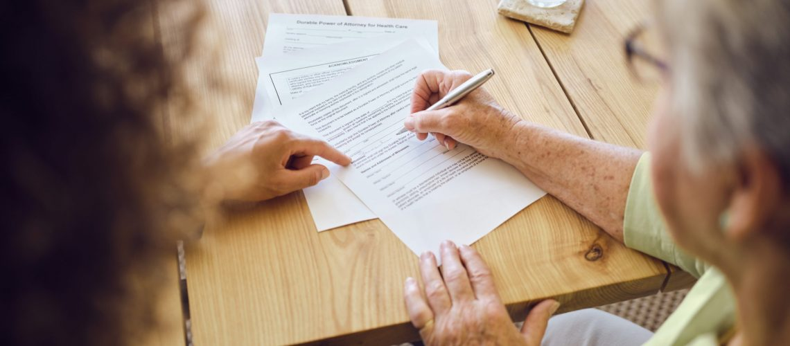 A senior aged woman signing documents with a financial adviser in her home.